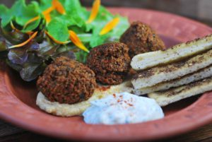 Falafels on a plate with flatbread, salad and houmus