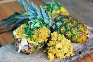Rice inside half of a pineapple on a chopping board with some rice piled up next to it