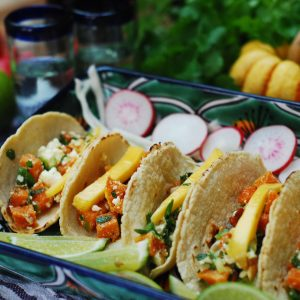 Roasted squash soft tacos with limes and radish surrounding the tacos