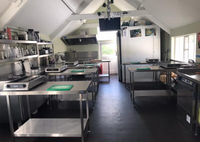 Natural Cookery School kitchen with socially-distanced work stations and tv screen above Erin